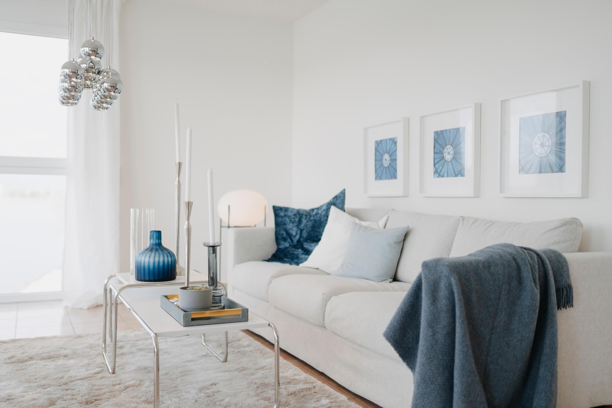 Lisa Treusch Immobilienfotografin Immobilienfotograf in Mainz und Umgebung Nahaufnahme eines Wohnzimmers in blau und weiss mit blauen und weissen Bildern an der Wand Sofa mit weissen und blauen Kissen und einer blauen Decke auf dem Couchtisch weisse Kerzen und eine blaue Vase und silbernen Pendelleuchten an der Decke