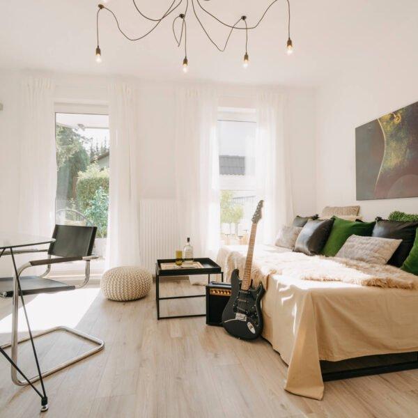 Lisa Treusch Fotografin Immobilienfotografie Home-Staging Nahaufnahme eines Wohnzimmers mit zwei hellen deckenhohen Fenstern weißen Vorhängen und einem großen Bild an der Wand ein weißen Sofa mit weißem Lammfell grünen udn schwarzen Kissen und einer E-Gitarre mit Verstärker und Schreibtisch im Industrial Stil