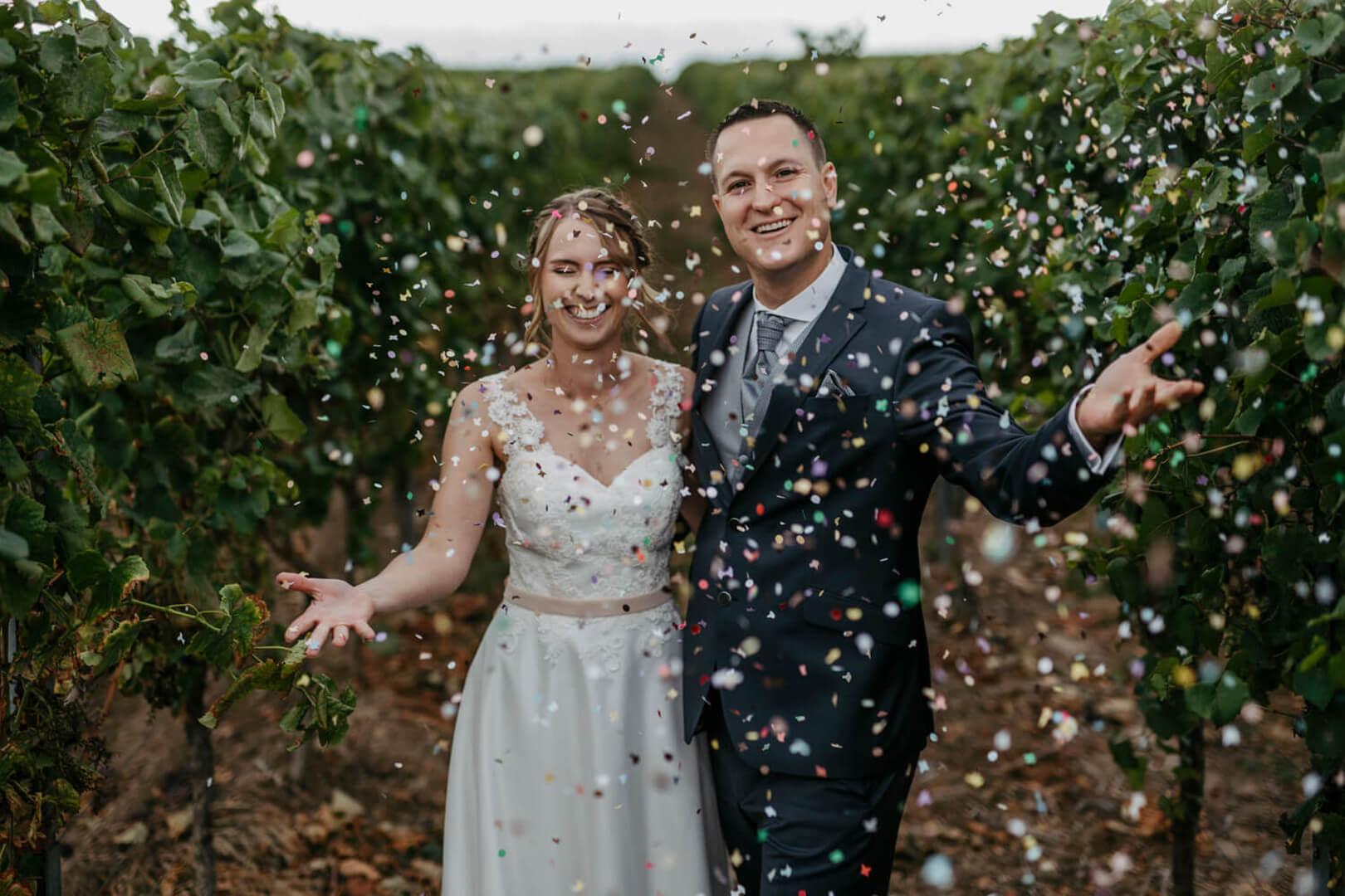 Lisa Treusch Hochzeitsfotografin Fotoshooting draußen Brautpaar in den Weinbergen wirft Konfetti witzige Hochzeitsbilder