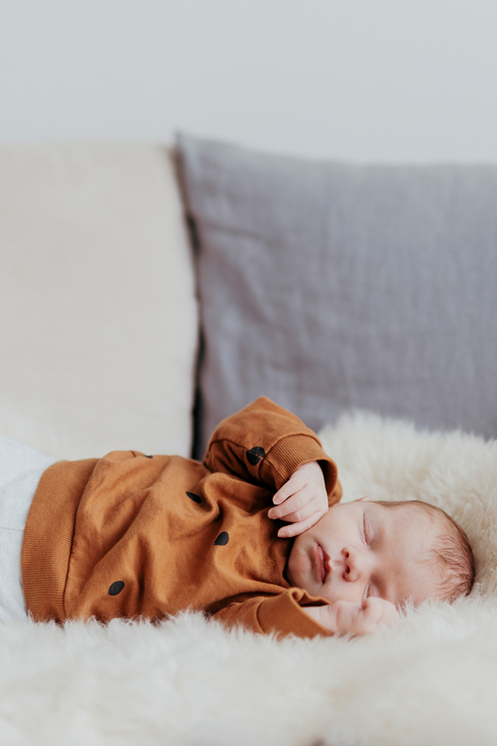 Neugeborenen Shooting Lisa Treusch Fotografin Mainz Neugeborenes liegt auf Lammfell und schläft
