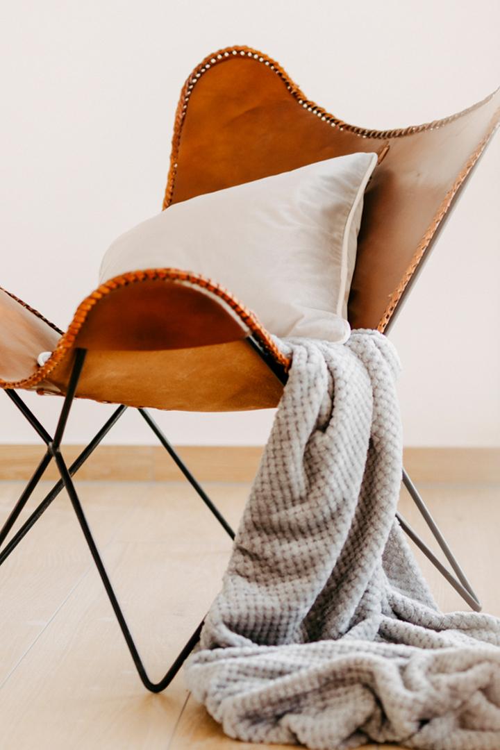 Immobilienfotografie Lisa Treusch Fotografin Mainz Nahhaufnahme eines Ledersessels mit Kissen und Wolldecke